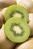 Two slices of kiwi fruit on whole kiwi fruits