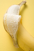 Banana, partly peeled, on yellow background