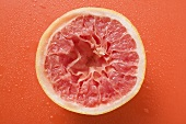 Squeezed pink grapefruit on orange background
