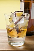 Rum and ice cubes with spices and pieces of fruit in glass