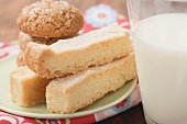 Biscuits and shortbread on plate, glass of milk