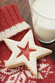 Jam-filled star biscuit on woollen mitten, glass of milk (Xmas)