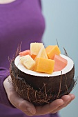 Woman holding hollowed-out coconut full of exotic fruit salad