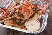 Salmon & prawn skewers with mint & sauce in aluminium dish