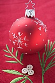 Red Christmas tree bauble on embroidered linen cloth
