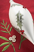 White tear-drop shaped Christmas bauble on red linen cloth