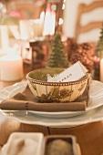 Weihnachtliches Gedeck mit Tischkarte bei Kerzenlicht
