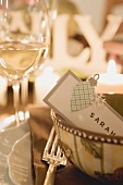 Christmas place-setting with place card, glasses of white wine