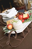 Small sleigh filled with cheese and apples for Christmas