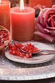 Pomegranate seeds on plate with spoon, red candles & rose