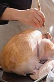 Brushing turkey with marinade