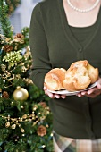 Woman holding plate of popovers (Christmas)