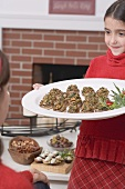 Girl serving platter of stuffed mushrooms (Christmas)