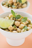 Chick-peas with lime wedges and herbs (close-up)