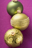 Three different Christmas baubles (green and gold)