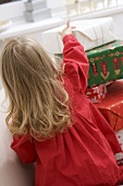 Small girl in front of pile of Christmas parcels