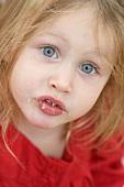 Kleines Mädchen mit Krümeln um den Mund