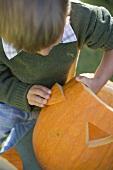 Small boy making pumpkin lantern