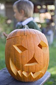 Carved pumpkin face for Halloween, child in background