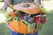 Man holding pumpkin decorated with flowers