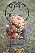 Pumpkin decorated with flowers on garden chair