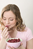 Woman smelling fresh raspberry