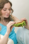 Woman holding wholemeal avocado and watercress sandwich