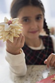 Girl with star biscuits on her finger