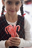 Girl holding candy canes
