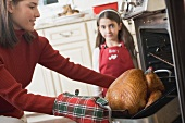 Young woman taking turkey out of oven, girl in background