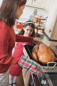 Young woman putting turkey on cooker, girl in background