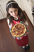 Girl holding freshly-baked fig tart (overhead view)