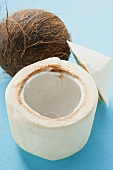 Fruchtfleisch einer Kokosnuss vor ganzer Kokosnuss