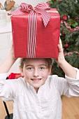 Girl balancing Christmas gift on her head
