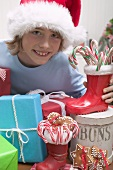 Boy in Father Christmas hat with gifts