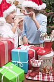 Girl and boy in Father Christmas hats with gifts