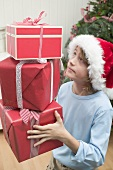 Boy in Father Christmas hat carrying pile of parcels