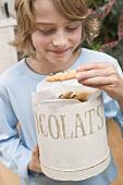 Junge nimmt Chocolate Chip Cookie aus Vorratsdose
