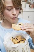 Junge isst Chocolate Chip Cookie aus Vorratsdose