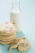 Nut biscuits, in a pile, in front of bottle of milk