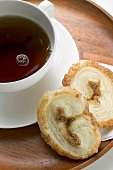 Palmiers (puff pastry biscuits) and cup of coffee