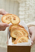 Hand taking palmier (puff pastry biscuit) from box