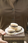 Woman holding macarons (small French cakes) on box