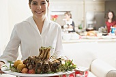 Young woman serving rack of pork for Christmas