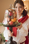 Woman holding fruit under glass cover (Christmas table decoration)