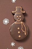 Snowman biscuit with chocolate icing on brown background