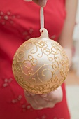 Woman holding gold Christmas bauble
