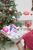 Woman holding box of Christmas baubles
