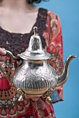 Woman holding Middle Eastern teapot
