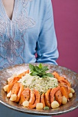 Woman serving couscous with pumpkin, mint and onions